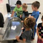 Children standing around a sink