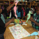 Children decorating a cake on a table