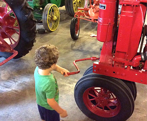 Child cranking a lever on a cart