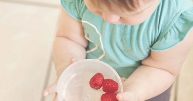 child with bowl of fruit berries