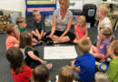 Children and teacher sit in a circle around a poster on the floor