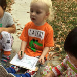 Child sitting outside, drawing on a clipboard