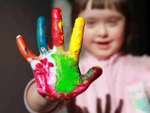 child with paint on hand