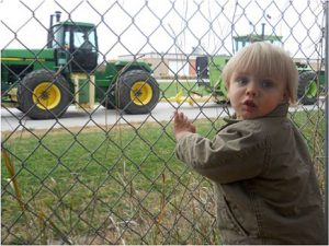 child looking at tractor