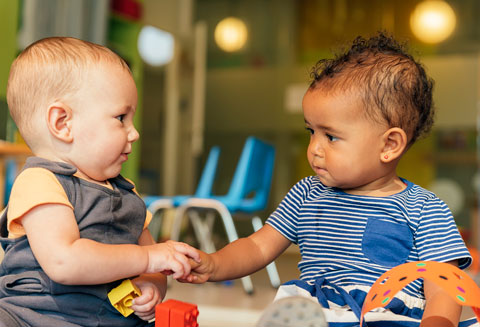 two toddlers touching hands