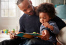 Father and child read a book together