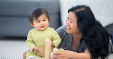 Mother building blocks with her baby