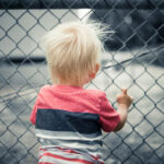 Child looking through a chain-link fence