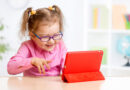 Little girl playing with a digital tablet on the countertop
