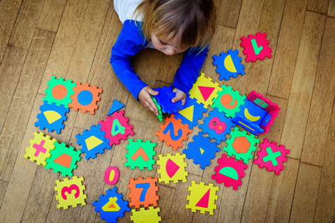 child plays with letter blocks