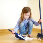 child with broom and dust pan