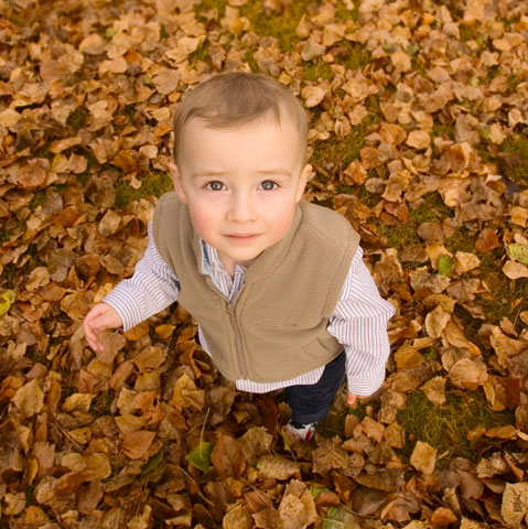 boy standing in leaves looking up at the sky