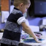 young boy painting with hands