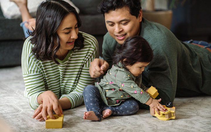 parents watch child play with toy