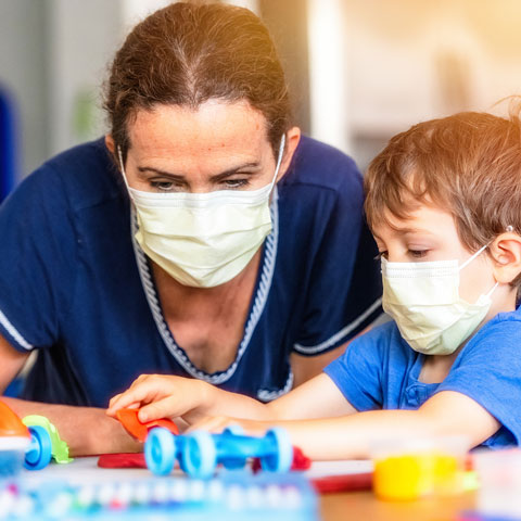 teacher and child wearing protective masks