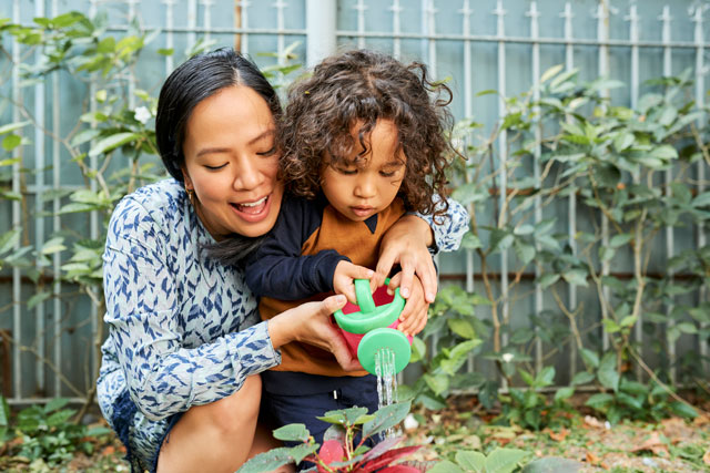 Mother and child watering a plant