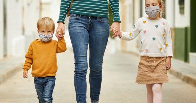 a parent walking with two children