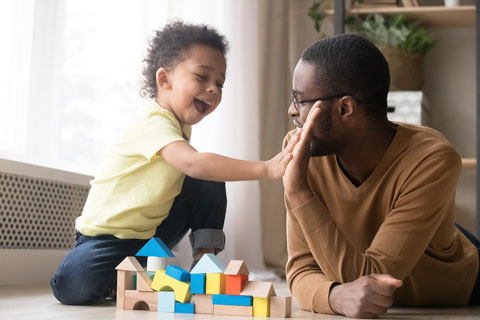 child and dad playing with blocks