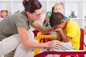 teacher assisting child