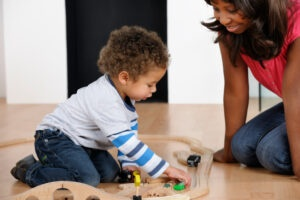 early childhood teacher watching toddler play with train