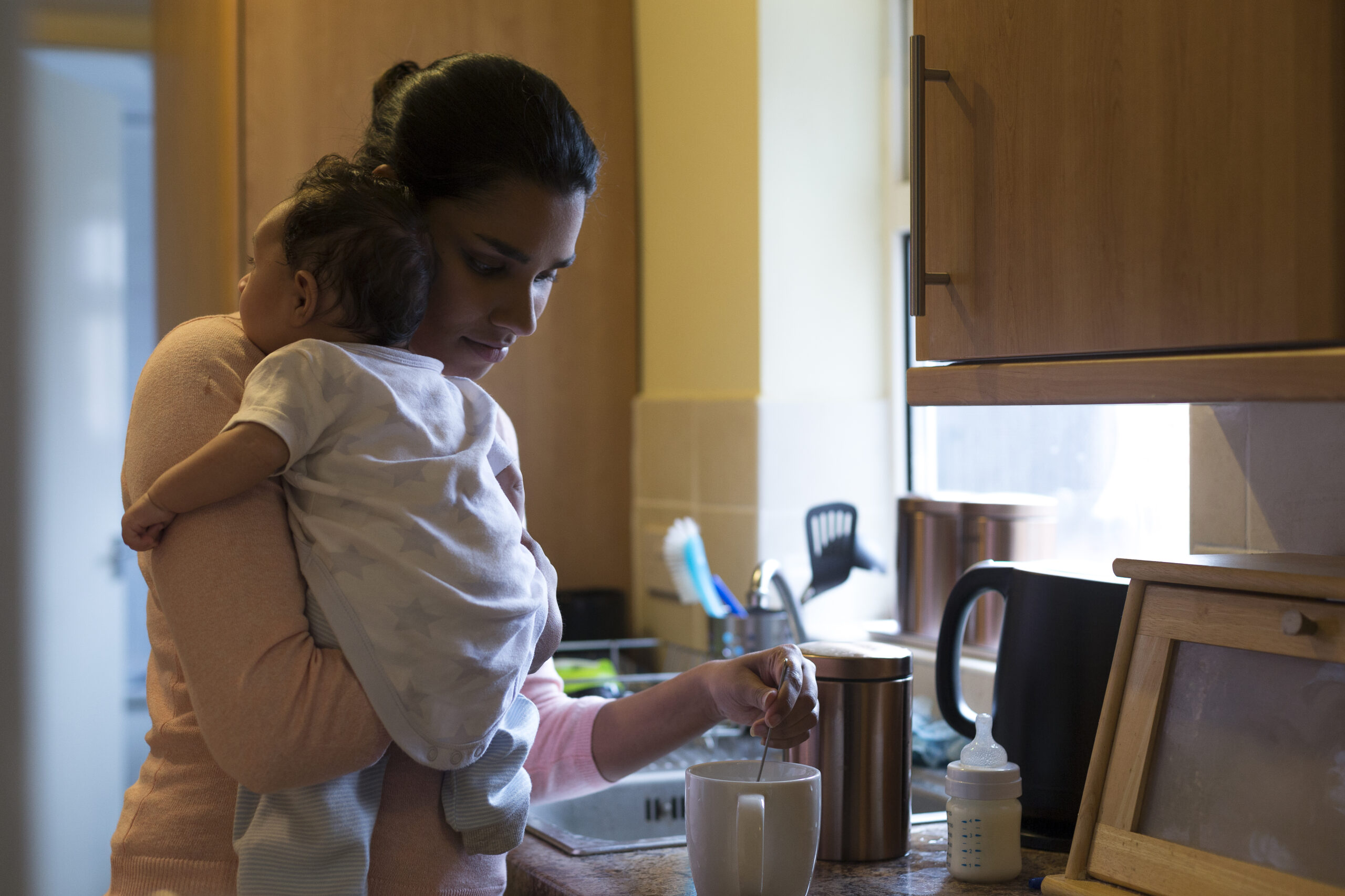 Mom holding infant making tea in the kitchen
